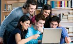 Abdorbed young students watching at laptop and study together at college library